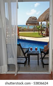 looking out through open door to drinks, pool, tropical grounds