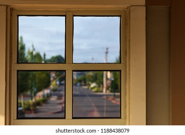 Looking out an urban window with clouds and a blue sky over a road