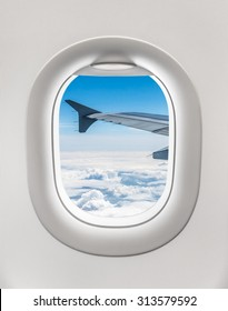 Looking out the window of a plane to the aircraft wing, blue sky and clouds