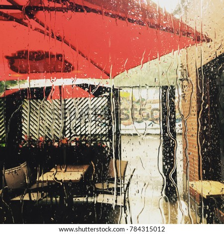 Looking out the window of a pub in Montreal during a rain storm. Water running down the glass window. Rain water running down window, heavy rain storm. Filter effect added.