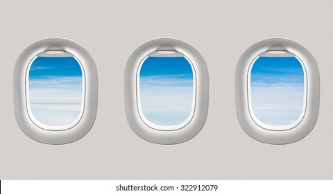 Looking out the windows of a plane to the beautiful blue sky and clouds