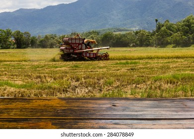 Looking out from a wooden table ,the blur image of farmers use harvest on the background for a product or other.
