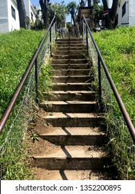 Looking up at a outdoor, city staircase with metal banisters