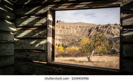 Looking outside at the dune, hoodoos and trees through a glassless window of an deserted wooden building. (BC Canada)