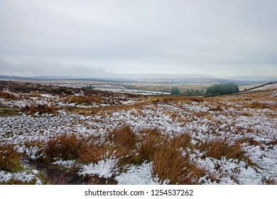 Looking over the baren and bleak landscape of the Dartmoor National Park with a light covering of snow, Devon, UK