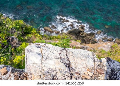 Looking over a cliff edge with blue sea below and Cliff edge and the sea. Stones worn smooth along the top of a cliff and a blue sea below.