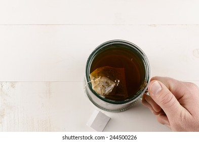 Looking over cup of tea with guys hand