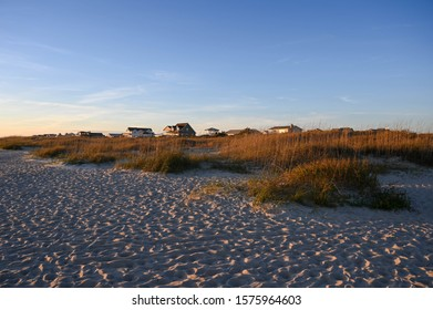 Looking over the dunes at a row of houses at the ocean. The sunset has turned the grass orange.