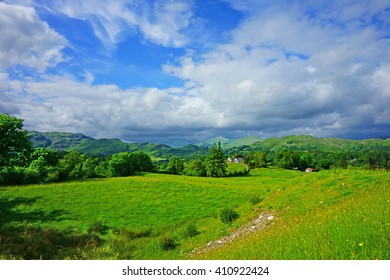 Looking over open countryside from near to the town of Ambleside towards the start of the mountain range called The Langdale Pikes, The Lake District, Cumbria, England, United Kingdom