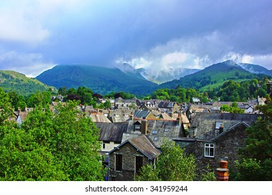 Looking over the roof tops of the town of Ambleside towards the start of the mountain range called The Langdale Pikes, The Lake District, Cumbria, England, United Kingdom