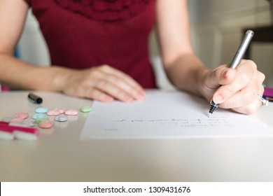 Looking over the shoulder of a woman writing a letter with Valentine's Day candy and children's art supplies