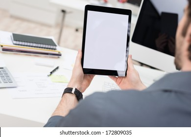 Looking over the shoulder of a young businessman sitting at his desk using a tablet computer with the blank white screen viewable
