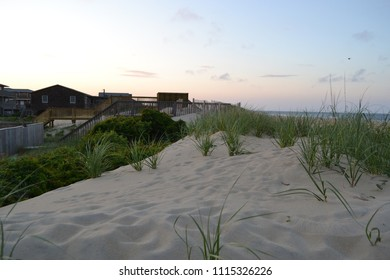 looking over some sand dunes at Kill Devil Hills in North Carolina as sunset unfolds.
