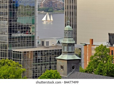 looking past the tall buildings of downtown Halifax towards the harbor, Tallship sailing by in between the buildings; Halifax Nova Scotia Canada