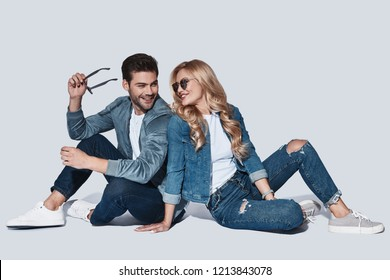 Looking perfect. Beautiful young couple in denim wear bonding and smiling while sitting against grey background