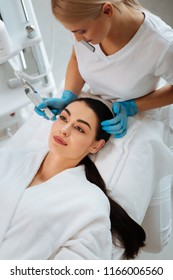 Looking perfect. Nice pleasant woman smiling while having a beauty procedure in the beauty salon