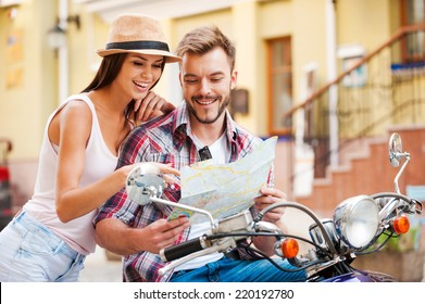 Looking for place to go. Beautiful young loving couple sitting on scooter together and examining map while woman pointing it and smiling