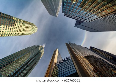 Looking up at a rainbow halo in the blue sky with tall city buildings