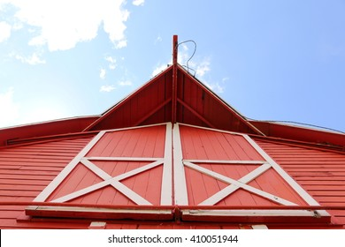 looking up at a red barn towards the blue sky.