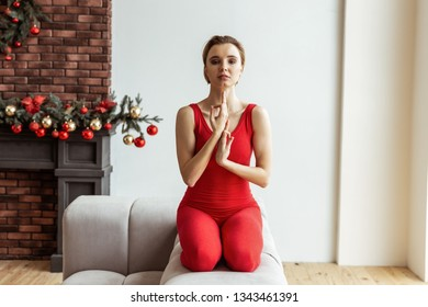 1440a05956333d Short-haired young woman in red outfit sitting on her knees and