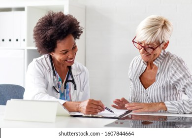 Looking at results of treatment mature woman in ambulance with her doctor