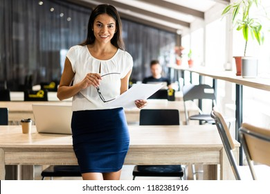 Looking for the right document. Beautiful young woman examining documents while standing near her table in office