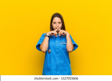 looking serious and displeased with both fingers crossed up front in rejection, asking for silence isolated against yellow wall
