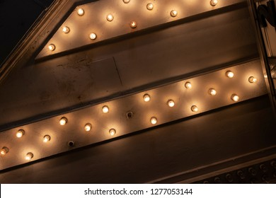 Looking up from the Sidewalk at Many Light Bulbs in a Theater Marquee Overhang Generic