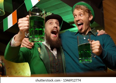 Looking silly. Dark-haired bearded young man wearing a leprechaun hat and his friend looking drunk