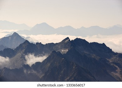 Looking South over the french pyrenees mountains from 3000m with swirling clouds enshrouding peaks.
