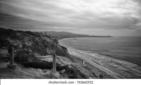 Looking south towards San Diego from Torrey Pines cliff. A surfer walks towards the beach as the waves crash into the coast.