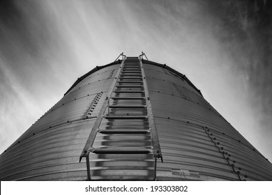 Looking up at a steel grain bin in black and white