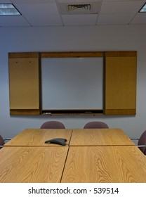 Looking straight down a conference table at a blank whiteboard