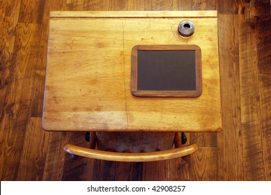 Looking straight down on an antique school desk isolated on a rough wooden floor.  Complete with ink bottle and small chalk board