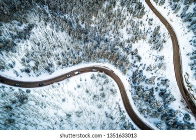 Looking straight down over Snow covered landscape forest and curvy windy Road cutting though the Mountains Aerial drone view in Santa Fe , New Mexico