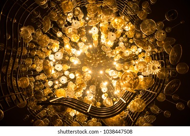 Looking straight up into a very large chandelier light fixture.