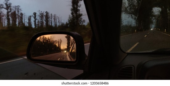 Looking at the sunset light in the rearview mirror.