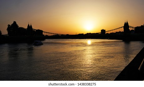 Looking in to the sunset over the river Thames with a the silhouette of Hammersmith Bridge, London, UK
