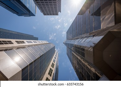 Looking up at tall skyscrapers from the ground on a sunny blue sky day