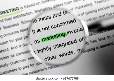 Looking at text with highlighted word MARKETING through magnifier, closeup