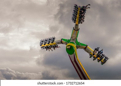 Looking up at thrill seekers on a fairground ride against a dramatic cloudy sky