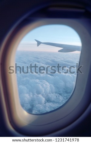 Looking through an airplane window towards the clouds sky