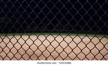 Looking through a baseball fence up close and seeing the field in the background.