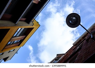 Looking up through buildings. Yellow paint. Blue sky with only one cloud. Lamp poste. Belgium  Brussels architecture