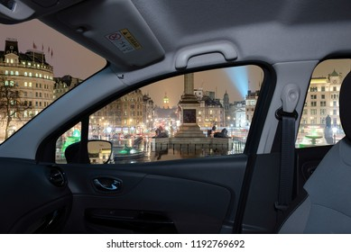Looking through a car window with view of Trafalgar Square at night with the Big Ben on the background, London, UK