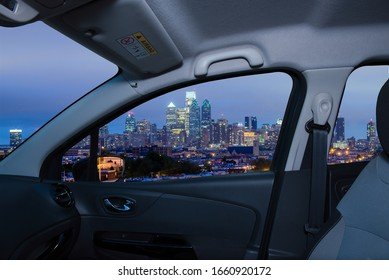 Looking through a car window with view of Philadelphia skyline at night as seen from the Stadium District, USA
