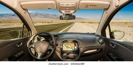 Looking through a car windshield with view over a hot desert road in Death Valley National Park, California, USA