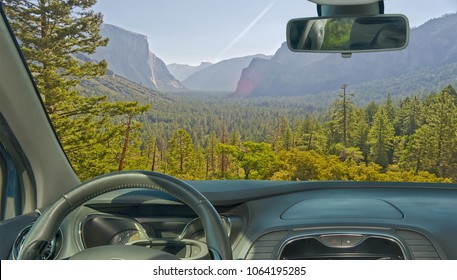 Looking through a car windshield with view of a beautiful green valley in Yosemite National Park, USA