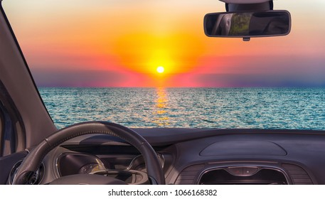 Looking through a car windshield with view of a scenic sunset on the mediterranean sea