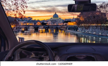 Looking through a car windshield with view of Saint Peter's Church during a wonderful sunset in Rome, Italy